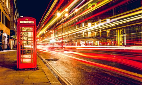 A London road with a red phone box.